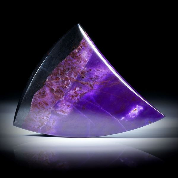 Sugilith Freiform 70.77ct.  Zahnform poliert, mit natürlichem Übergang in Manganerz, ca.42x38x7mm